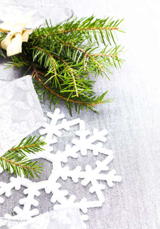 Christmas tree branch and White Christmas ornaments on soft grey background. Christmas Time Decorations with snowflake. photo