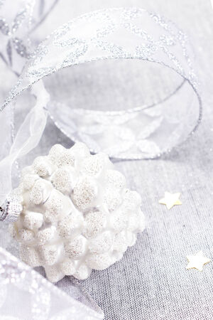 Christmas Decorations with white pine cone, silver  stars and silver ribbon close up. Christmas card with copyspace for greeting text, vertical. White Christmas.  photo