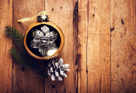 Vintage Christmas  decorations on wooden background. Golden ball and pine cone on old wood board with copyspace for greeting text. photo