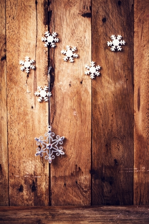 Christmas background with festive ornaments and snowflakes on old  wooden wall. Old fashioned Christmas Decoration with copyspace.