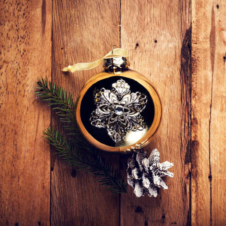 Vintage Christmas  decorations on wooden background. Golden ball and pine cone on old wood table. photo