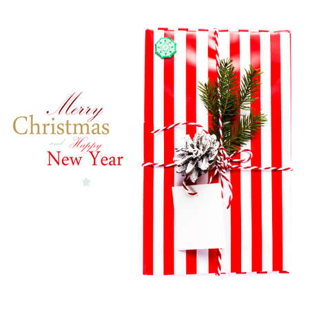 Christmas gift box and decorations isolated on white background. Vintage gift box with red paper package and blank gift tag  (with easy removable sample text) photo