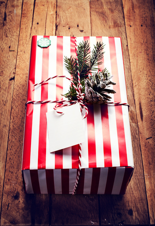Christmas gift box and decorations on wooden background. Vintage gift box with red paper package and blank gift tag. Christmas gift card.  photo