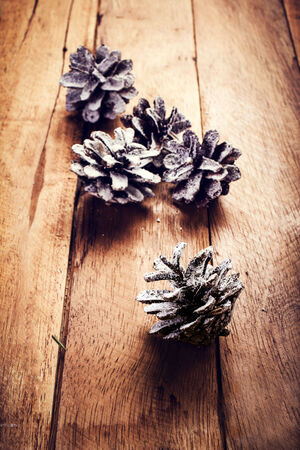 Christmas  decorations on wooden background. Pine cones on old wood board сдщыу гз with copyspace for greeting text. photo
