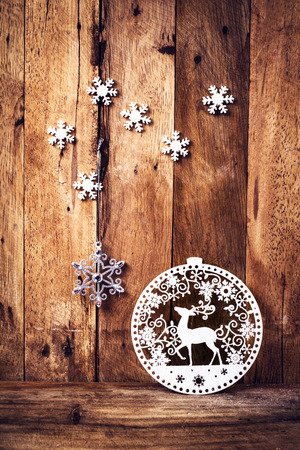 Christmas background with holiday decorations and white snowflakes  over wooden board.  Vintage Christmas card or invitation with copyspace.