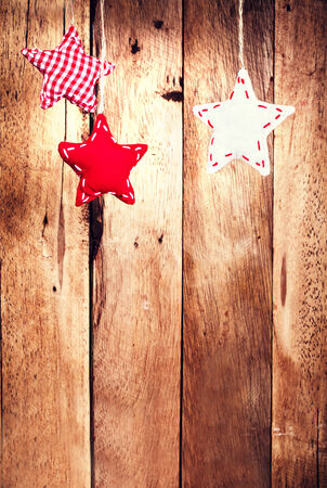 Christmas background with hangind red stars over wooden wall. Holiday card with decorations. Vintage Christmas card or invitation with copyspace. photo