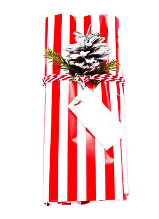 Christmas gift box and decorations isolated on white background. Vintage gift box with red paper package and blank gift tag. photo