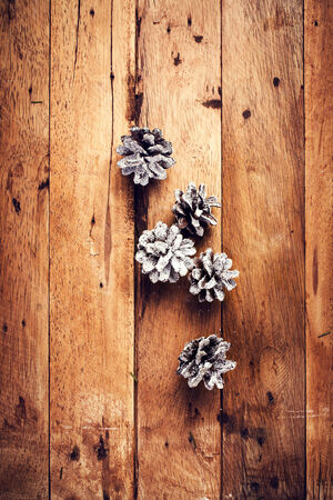 Christmas  decorations on wooden background. Pine cones on old wood board with copyspace for greeting text. photo