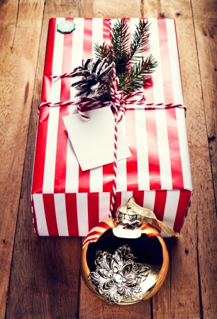 Christmas gift box and decorations on wooden background. Vintage gift box with red paper package and blank gift tag.  photo