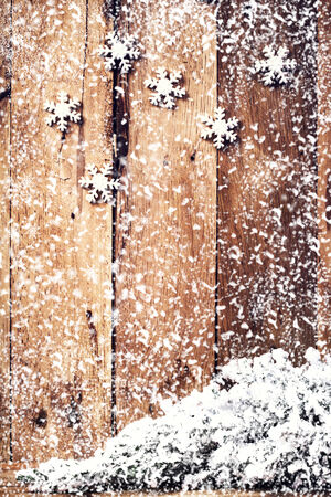 snowflake border: Christmas background with festive ornaments and falling snowflakes over old wooden wall. Vintage Christmas card or invitation with copyspace.