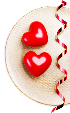 Two Red hearts on a golden plate isolated on white with festive ribbon. Love, harmony and Valentines day concept. Valentines Day background.  photo