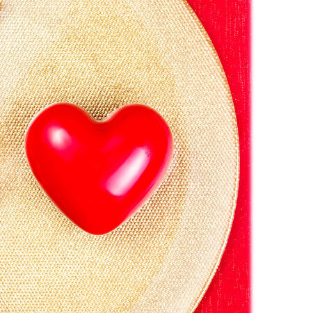 Red Heart on golden plate on red tablecloth isolated on white background. Valentines Day background. Valentines Day Card with copyspace photo