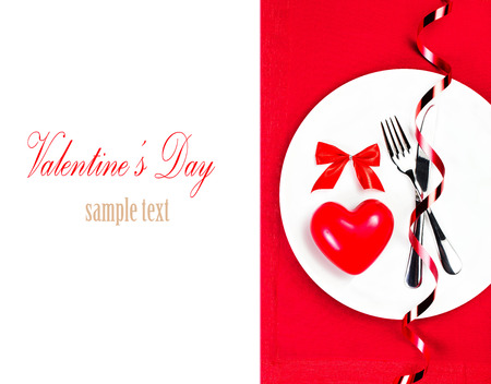 Valentines Day table setting place with copyspace. Red Heart on a white plate plate isolated on white background. Valentine Day Card  photo