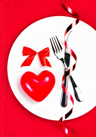 Red Heart on a white plate plate on festive napkin with red bow.  Valentines Day Card with copyspace. Valentines Day background.  photo