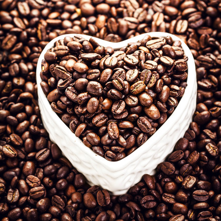 Roasted Coffee Beans in a Heart shaped  bowl at Valentine Day Holiday over coffee beans background close up.  Coffee Beans in Shape of Heart  for Valentine's Day Card.  photo