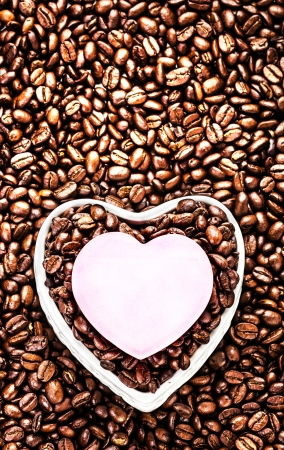Roasted Coffee Beans with Heart Shaped Paper Sheet over coffee bean background close up. Wedding, love, holiday,  Valentine Day Card. Love Coffee at Valentine's Day. photo