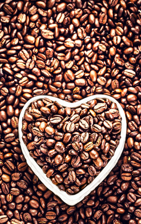 Roasted Coffee Beans in a white  Heart shaped  bowl at Valentine Day with copy space for greeting text. Coffee Beans in Shape of Heart  for Valentines Day Card.  photo