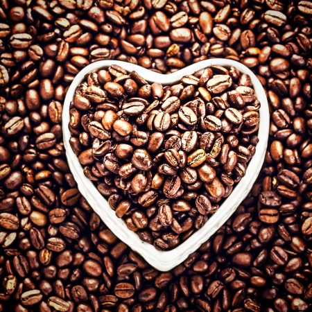 Roasted Coffee Beans in a Heart shaped  bowl at Valentine Day Holiday over coffee beans background.  Coffee Beans in Shape of Heart  for Valentine's Day Card. Top view. photo