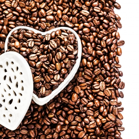 Roasted Coffee Beans in a white Heart shaped  box at Valentine Day Holiday over coffee beans background isolated. Wedding, love, black, frame. Valentines Day Card.  photo