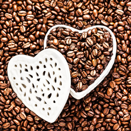 Roasted Coffee Beans in a white Heart shaped  box at Valentine Day Holiday over coffee beans background with copyspace for text.  Wedding, love, black, frame. photo