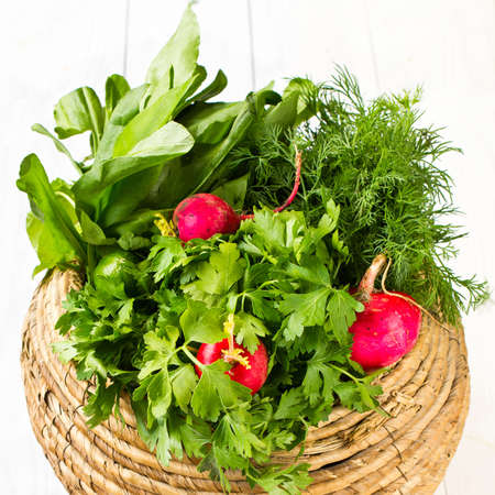 A bunch of fresh different vegetables in a bowl wicker basket on white wooden background photo