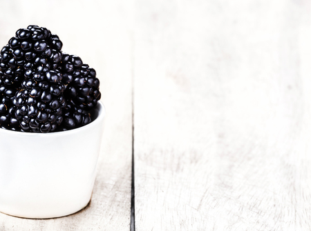 Sweet Fresh  Blackberries in a white bowl on  bright wooden background close up with copy space.  photo