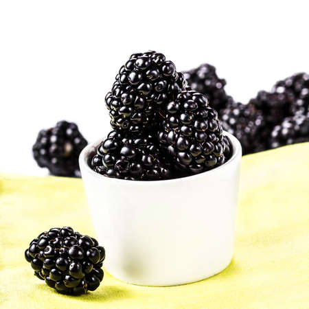 Sweet Fresh  Blackberries in a white bowl on a yellow napkin isolated on white background, closeup. photo