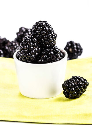 Blackberries in a white bowl isolated on white background, closeup. photo