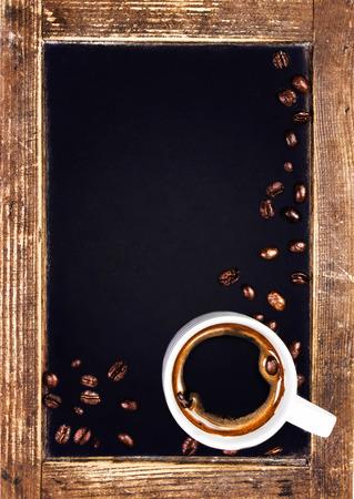 コーヒー カップとビンテージ スレート チョーク ボードのクローズ アップ。木製黒板トップ ビューにロースト コーヒー豆とコーヒー カップ。 写真素材