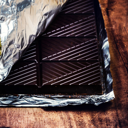 Chocolate bar in foil on old wooden textured background close up.  photo