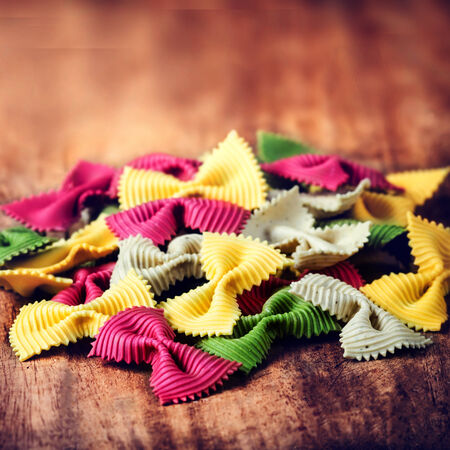 Fresh Italian Colourful Pasta on old wooden background close up.  Raw Bow tie  pasta macro. Italian Food. photo