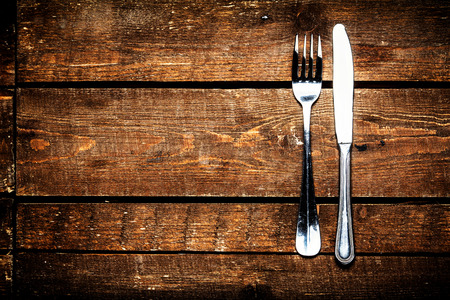 Silver Knife and fork over wooden table with copy space. Diet Food concept.