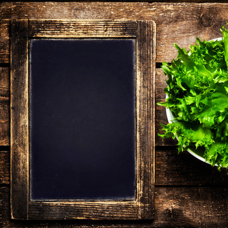 web menu: Black chalkboard for menu and fresh salad over wooden . Diet Food Restaurant and healthy lifestyle concept.