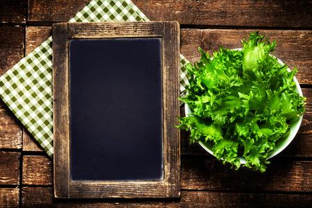 黒の黒板メニューと木製の上の新鮮なサラダのため。ダイエット食品レストラン、健康的なライフ スタイルのコンセプト。