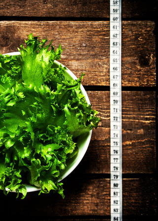 Fresh Fitness salad and measuring tape on rustic wooden table.  Diet and healthy lifestyle concept. photo
