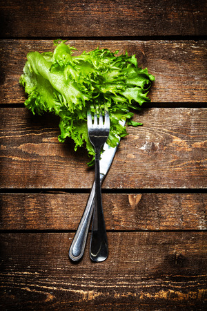 Fresh Salad over wooden table with knife and fork.  Diet Food and healthy lifestyle concept macro. photo