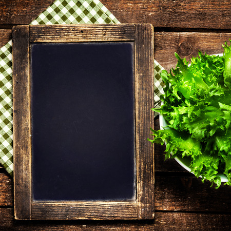 Blank menu blackboard over vintage wooden background with green fresh salad in a bowl.
