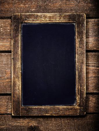 card board: Aged  menu blackboard over vintage wooden background. Empty Chalkboard. Stock Photo