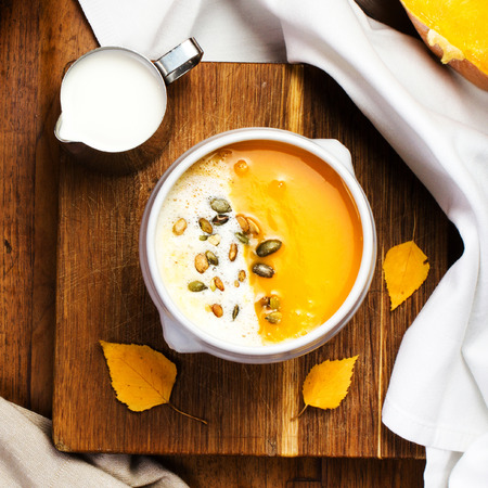 Pumpkin Soup with whipped cream and pumpkin seeds in a white plate over wooden background.  photo