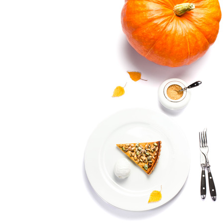 Slice of fresh Pumpkin Pie with whipped cream and pumpkin seeds on white plate isolated. Beautiful autumn Pumpkin thanksgiving pie photo