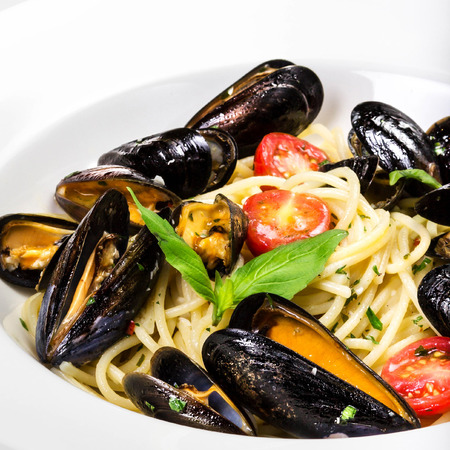 Pasta with mussels and basil for a tasty sea food meal macro photo