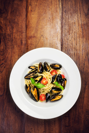 seafood platter: Seafood  Pasta with mussels, cherry tomato  and basil in white plate on wooden table, top view