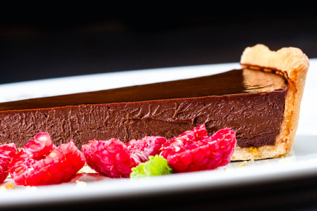 Piece of Sweet chocolate cake with fresh raspberries close up. Stock Photo