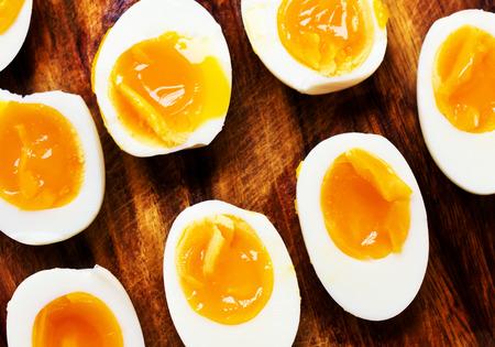 hard boiled: Hard boiled eggs, sliced in halves on wooden background Stock Photo