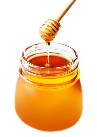 白い背景に分離された蜂蜜ディッパーとガラスの瓶に蜂蜜をクローズ アップ。新鮮な蜂蜜スティック、マクロ。 写真素材