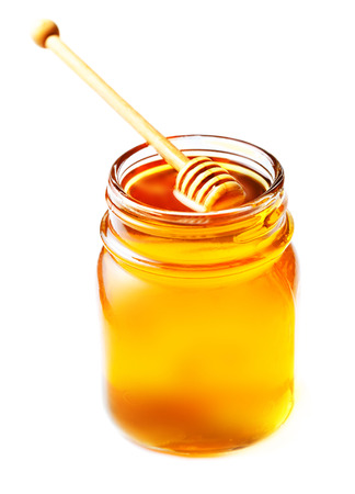 honey liquid: Honey in a glass jar with honey dipper  isolated on white background close up. Fresh honey with a stick, macro.