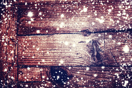winter card: Christmas decoration with falling snowflakes and Xmas lights on dark wooden board - Christmas Card with copy space for greeting text Stock Photo