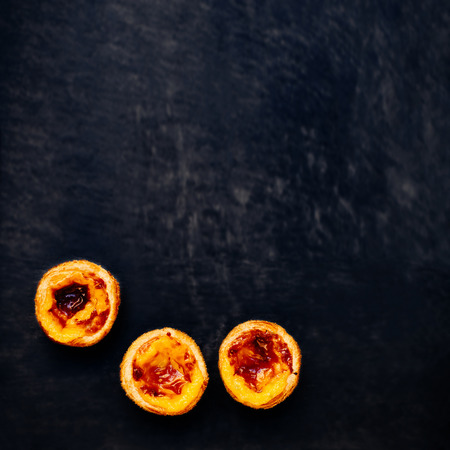 nata: Pasteis de nata, typical Portuguese egg tart over black background with blank copy space for text Stock Photo
