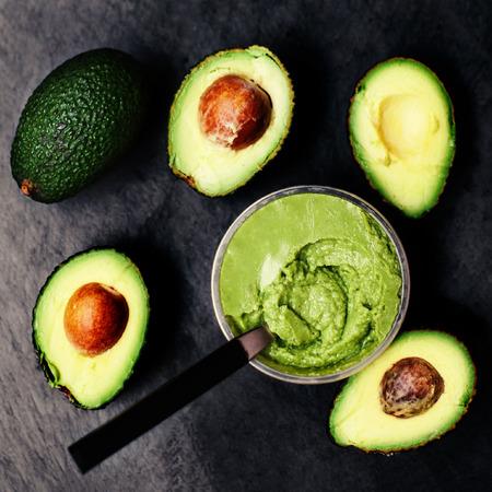 Halved avocados over black background.