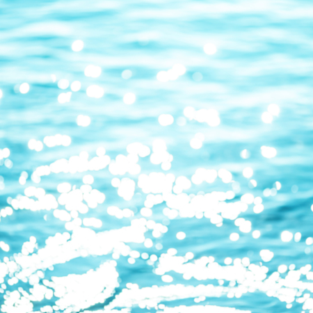 Abstract Summer background with sparkling natural bokeh over blue water.